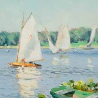 Four white sailboats in water, trees in the distance. Row boats along the shore bottom right corner of image.